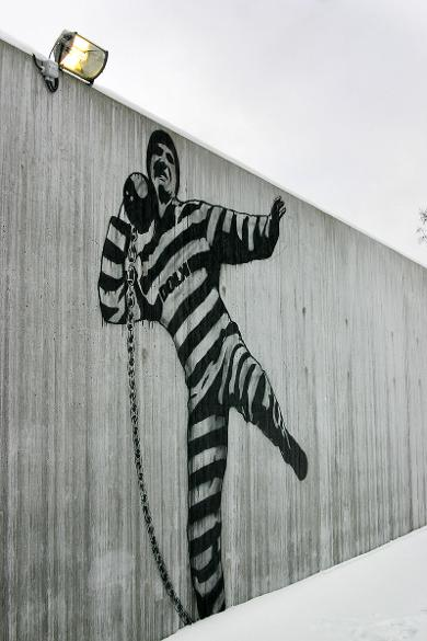 Graffiti Art by Dolk within the prison walls showing prisoner trying to throw away a ball and chain